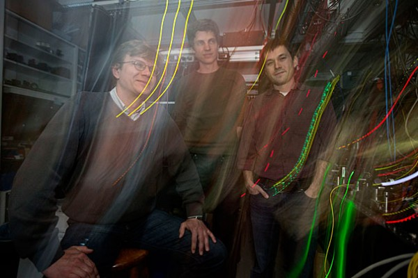 Mikhail Lukin, (glasses) Professor of Physics, Tobias Ticke (green shirt)  and Jeff Thompson, (red shirt) have succeeded in building switches which consist of a single atom, which can be turned on or off using a single photon. The switches could one day be the backbone of ultra-secure networks of quantum computers in the Lyman Lab at Harvard University. Kris Snibbe/Harvard Staff Photographer